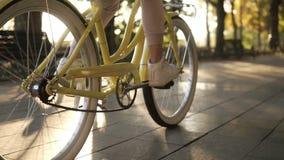 Θηλυκά απρόσωπα πόδια που περπατούν με το ποδήλατο στο στρωμένο ενεργό τρόπο ζωής οδικής κοντά επάνω πλάγιας όψης Η γυναίκα κοριτ απόθεμα βίντεο
