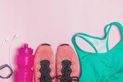 Θηλυκά εξαρτήματα ικανότητας: πάνινα παπούτσια, μπουκάλι με το νερό και αθλητικός στηθόδεσμος στοκ εικόνες
