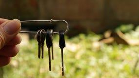 Θηλυκά κλειδιά εκμετάλλευσης χεριών στην καρφίτσα ασφάλειας στοκ εικόνες