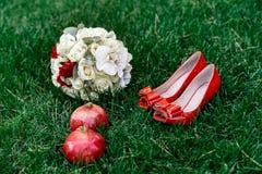 Θηλυκά κόκκινα γαμήλια παπούτσια μόδας με την ανθοδέσμη νυφών ` s άσπρων τριαντάφυλλων και δύο κόκκινων γρανατών στο πράσινο υπόβ Στοκ Φωτογραφία