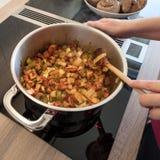 Θηλυκά λαχανικά αργού ψησίματος χεριών με το ξύλινο κουτάλι Στοκ εικόνα με δικαίωμα ελεύθερης χρήσης