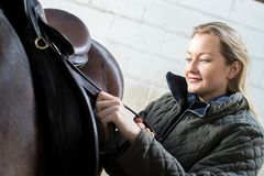 Θηλυκά λουριά σελών ρύθμισης ιδιοκτητών στο σταύλο με το άλογο Στοκ Εικόνα