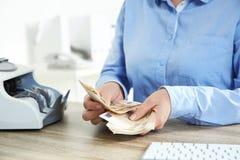 Θηλυκά μετρώντας χρήματα αφηγητών στο τμήμα μετρητών στοκ εικόνες