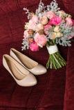 Θηλυκά μπεζ γαμήλια παπούτσια μόδας στην εστίαση με την κομψή ανθοδέσμη νυφών ` s στους τόνους κρητιδογραφιών από την εστίαση Στοκ εικόνα με δικαίωμα ελεύθερης χρήσης