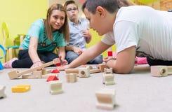 Θηλυκά παιδιά διδασκαλίας εκπαιδευτικών για να χτίσει ένα κύκλωμα τραίνων στοκ εικόνες