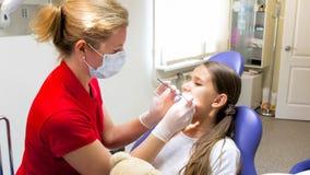 Θηλυκά παιδιατρικά δόντια κοριτσιών επιθεώρησης οδοντιάτρων με τα όργανα Στοκ εικόνες με δικαίωμα ελεύθερης χρήσης
