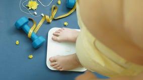 Θηλυκά πλήρη γυμνά πόδια στάσεων στις κλίμακες σε ένα μπλε υπόβαθρο Διατροφή, ικανότητα απόθεμα βίντεο