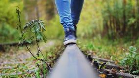 Θηλυκά πόδια ξένοιαστων περιπάτων κατά μήκος του σιδηροδρόμου Το κορίτσι πηγαίνει στις ράγες προς τη κάμερα 3840x2160 απόθεμα βίντεο