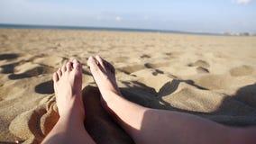Θηλυκά πόδια που κάνουν ηλιοθεραπεία στην παραλία απόθεμα βίντεο