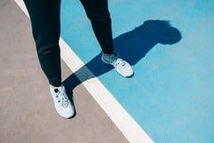 Θηλυκά πόδια στα πάνινα παπούτσια και τα μαύρα αθλητικά εσώρουχα στοκ φωτογραφία με δικαίωμα ελεύθερης χρήσης