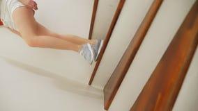 Θηλυκά πόδια στα πάνινα παπούτσια που τρέχουν κατά μήκος μιας ξύλινης σκάλας απόθεμα βίντεο