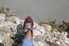Θηλυκά πόδια στην άκρη του απότομου βράχου Στοκ εικόνα με δικαίωμα ελεύθερης χρήσης