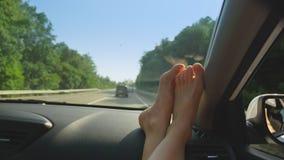 Θηλυκά πόδια στο ταμπλό του αυτοκινήτου, από την πλευρά του καθίσματος επιβατών η έννοια των καλοκαιρινών διακοπών και του ταξιδι απόθεμα βίντεο