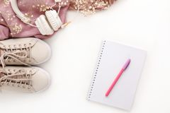 Θηλυκά ρόδινα εξαρτήματα μόδας καθορισμένα Πάνινα παπούτσια, ακουστικά και λουλούδια στοκ εικόνες