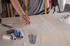 Θηλυκά σκίτσα σχεδίων σχεδιαστών μόδας για τα ενδύματα στο ατελιέ Στοκ Φωτογραφίες