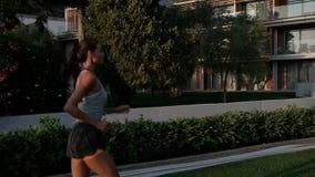 Θηλυκά τρεξίματα αθλητών μέσω του πράσινου χορτοτάπητα τη θερινή ημέρα υπαίθρια φιλμ μικρού μήκους