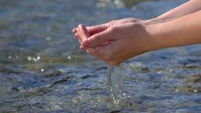 Θηλυκά χέρια γυναικών που αρπάζουν και που ανυψώνουν το κρύσταλλο - σαφές γλυκό νερό στον ποταμό βουνών υπαίθρια, πτώσεις στην επ φιλμ μικρού μήκους