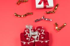 Θηλυκά χέρια και ελάφια Χριστουγέννων στα κόκκινα γάντια Στοκ εικόνες με δικαίωμα ελεύθερης χρήσης