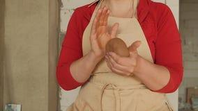 Θηλυκά χέρια κινηματογραφήσεων σε πρώτο πλάνο που κυλούν τη σφαίρα αργίλου πρίν εργάζεται σε μια ρόδα αγγειοπλαστικής απόθεμα βίντεο