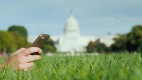 Θηλυκά χέρια με ένα smartphone Στο χορτοτάπητα, στα πλαίσια του Capitol στην Ουάσιγκτον Ταξίδι και μελέτη μέσα φιλμ μικρού μήκους