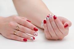 Θηλυκά χέρια με το μανικιούρ, κόκκινη στιλβωτική ουσία καρφιών, που σύρουν με τα κεράσια Άσπρη ανασκόπηση Στοκ Εικόνες