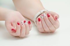 Θηλυκά χέρια με το μανικιούρ, κόκκινη στιλβωτική ουσία καρφιών, που σύρουν με τα κεράσια Άσπρη ανασκόπηση Στοκ φωτογραφίες με δικαίωμα ελεύθερης χρήσης
