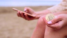 Θηλυκά χέρια με το bitcoin και το κινητό τηλέφωνο απόθεμα βίντεο