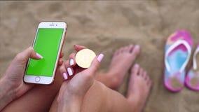 Θηλυκά χέρια με το bitcoin και το κινητό τηλέφωνο φιλμ μικρού μήκους
