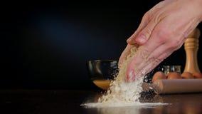 Θηλυκά χέρια που ανατρέπουν το αλεύρι στον πίνακα Στοκ εικόνα με δικαίωμα ελεύθερης χρήσης