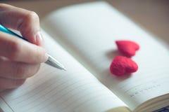 Θηλυκά χέρια που γράφουν στο ανοικτό σημειωματάριο με το ζεύγος λίγη κόκκινη καρδιά στοκ φωτογραφία με δικαίωμα ελεύθερης χρήσης