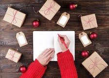 Θηλυκά χέρια που γράφουν την επιστολή Χριστουγέννων στο ξύλινο υπόβαθρο με τα δώρα και τις διακοσμήσεις Στοκ φωτογραφία με δικαίωμα ελεύθερης χρήσης