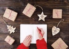 Θηλυκά χέρια που γράφουν τον κατάλογο δώρων Χριστουγέννων σχετικά με χαρτί για το ξύλινο υπόβαθρο με τα δώρα και τις ετικέτες Στοκ φωτογραφία με δικαίωμα ελεύθερης χρήσης