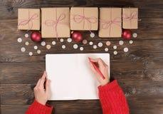 Θηλυκά χέρια που γράφουν τον κατάλογο δώρων Χριστουγέννων σχετικά με χαρτί για το ξύλινο υπόβαθρο με τα δώρα και τις ετικέτες Στοκ εικόνα με δικαίωμα ελεύθερης χρήσης