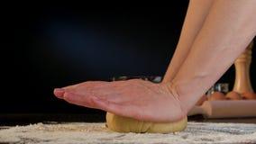 Θηλυκά χέρια που ζυμώνουν τη ζύμη στον πίνακα Στοκ Εικόνα