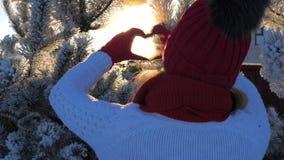 Θηλυκά χέρια που κάνουν τη φλόγα ήλιων εκμετάλλευσης χειρονομίας μορφής καρδιών στις ακτίνες χειμερινού ηλιοβασιλέματος απόθεμα βίντεο