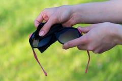 Θηλυκά χέρια που καθαρίζουν τα μαύρα και ρόδινα γυαλιά ηλίου υπαίθρια στοκ εικόνες