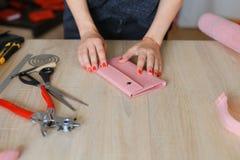 Θηλυκά χέρια που κατασκευάζουν το ρόδινο πορτοφόλι δέρματος με τα εργαλεία στο ατελιέ στοκ εικόνες