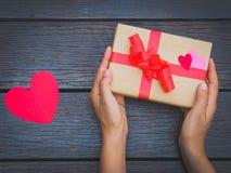 Θηλυκά χέρια που κρατούν ένα κιβώτιο δώρων στον ξύλινο πίνακα Στοκ Φωτογραφία