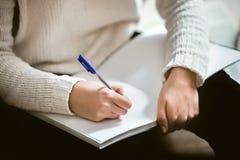 Θηλυκά χέρια που κρατούν μια μάνδρα και ένα σημειωματάριο Στοκ Φωτογραφία