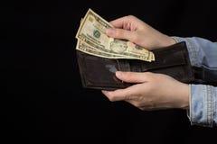 Θηλυκά χέρια που κρατούν τα δολάρια από ένα πορτοφόλι σε ένα μαύρο υπόβαθρο, κινηματογράφηση σε πρώτο πλάνο στοκ εικόνες