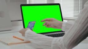 Θηλυκά χέρια που κρατούν την πιστωτική κάρτα και που δακτυλογραφούν στο lap-top απόθεμα βίντεο
