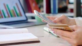 Θηλυκά χέρια που κρατούν την πιστωτική κάρτα και το τηλέφωνο Γυναίκα που εισάγει το αριθμό πιστωτικής κάρτας απόθεμα βίντεο