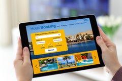 Θηλυκά χέρια που κρατούν την ταμπλέτα με app την κράτηση ξενοδοχείων στην οθόνη Στοκ φωτογραφία με δικαίωμα ελεύθερης χρήσης