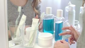 Θηλυκά χέρια που κρατούν τους φακούς ματιών για τη χρησιμοποίηση του μπροστινού καθρέφτη στο εγχώριο λουτρό απόθεμα βίντεο