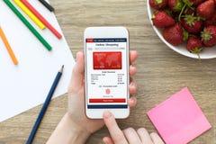 Θηλυκά χέρια που κρατούν το άσπρο τηλέφωνο με app τη σε απευθείας σύνδεση οθόνη αγορών Στοκ Εικόνες