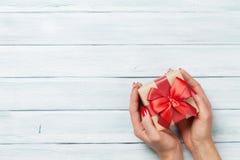 Θηλυκά χέρια που κρατούν το δώρο επάνω από τον ξύλινο πίνακα Στοκ φωτογραφία με δικαίωμα ελεύθερης χρήσης