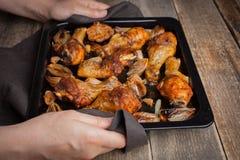 Θηλυκά χέρια που κρατούν το καυτό φύλλο ψησίματος από ψημένα τα φούρνος πόδια κοτόπουλου με τα κρεμμύδια και το σκόρδο Μια γυναίκ Στοκ φωτογραφία με δικαίωμα ελεύθερης χρήσης