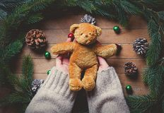Θηλυκά χέρια που κρατούν το teddybear παιχνίδι Χριστουγέννων Στοκ Εικόνα