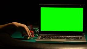 Θηλυκά χέρια που κτυπούν το lap-top, τσιπ πόκερ γύρω, πειρασμός να παίξει on-line απόθεμα βίντεο