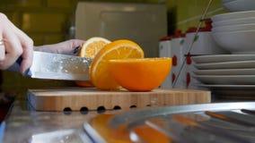 Θηλυκά χέρια που κόβουν το πορτοκάλι στον ξύλινο πίνακα πινάκων στην κουζίνα Στοκ φωτογραφία με δικαίωμα ελεύθερης χρήσης